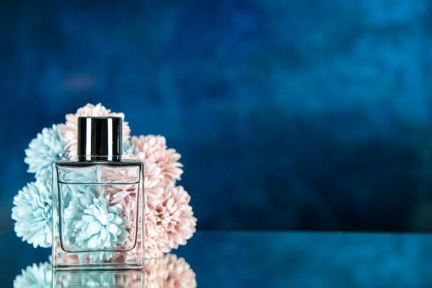 Fiori di bottiglia di profumo vista frontale su sfondo blu scuro con posto libero