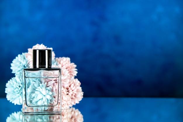 Vista frontale dei fiori della bottiglia di profumo su uno spazio libero di sfondo sfocato blu scuro