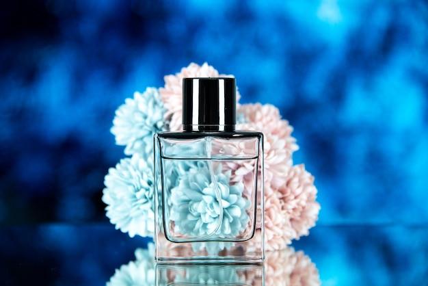 Vista frontale dei fiori della bottiglia di profumo su sfondo sfocato blu scuro con spazio libero