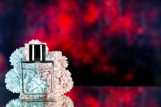 La bottiglia di profumo di vista frontale fiorisce sullo spazio libero del fondo vago astratto rosso scuro
