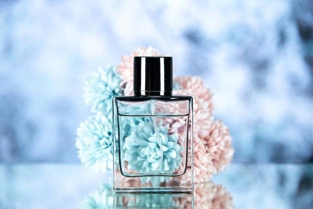 Vista frontale della bottiglia di profumo e dei fiori su sfondo sfocato blu ghiaccio
