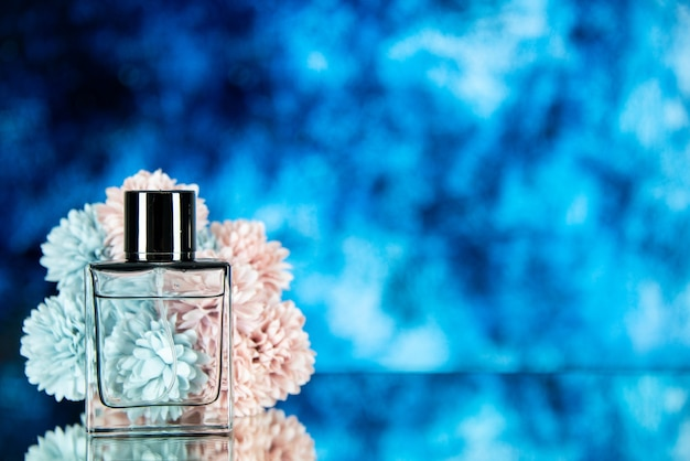 Fiori della bottiglia di profumo di vista frontale isolati sullo spazio libero del fondo blu dell'oceano