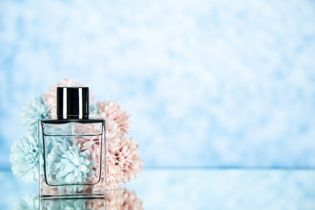 Fiori di bottiglia di profumo vista frontale su sfondo azzurro spazio libero