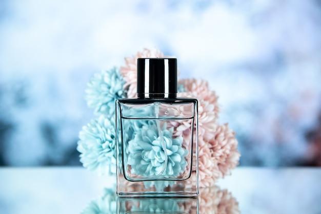 Vista frontale della bottiglia di profumo e dei fiori su sfondo azzurro sfocato