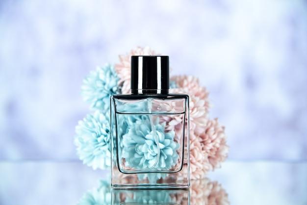 Fiori della bottiglia di profumo di vista frontale sullo spazio libero del fondo vago leggero