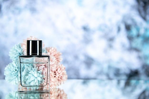 Fiori della bottiglia di profumo di vista frontale su fondo grigio chiaro con lo spazio della copia
