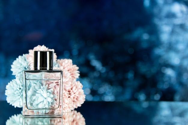 La bottiglia di profumo di vista frontale fiorisce sullo spazio libero del fondo vago blu dell'oceano