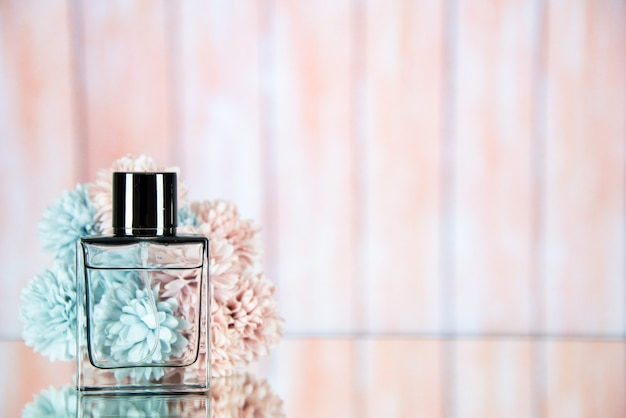 Вид спереди флакон духов цветы на бежевом размытом фоне свободное пространство