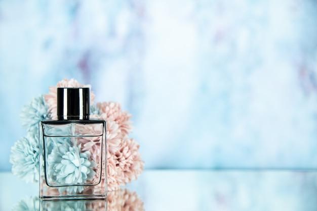 水色の背景の空きスペースに正面図の香水瓶の花