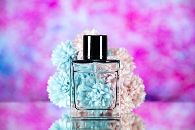 Vista frontale dei fiori della bottiglia di profumo sullo spazio libero del fondo vago rosa