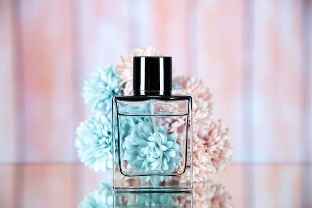 Vista frontale della bottiglia di profumo davanti ai fiori su beige sfocato