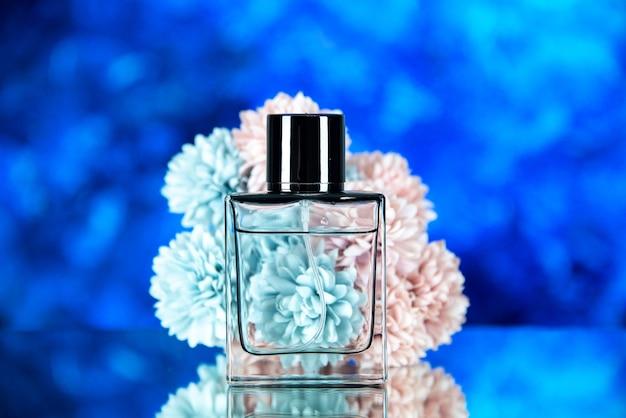 Vista frontale della bottiglia di profumo davanti ai fiori su blu sfocato