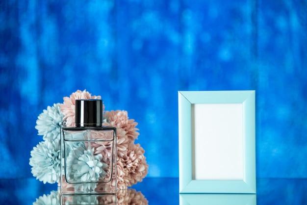 전면 보기 향수 병 파란색 배경에 작은 파란색 사진 프레임 꽃