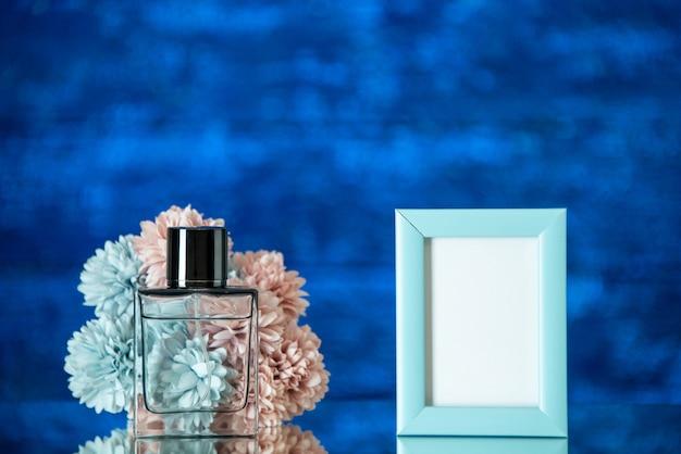 전면 보기 향수 병 파란색 흐리게 배경에 작은 파란색 사진 프레임 꽃