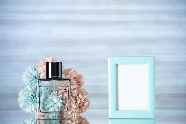 전면 보기 향수 병 작은 파란색 사진 프레임 꽃