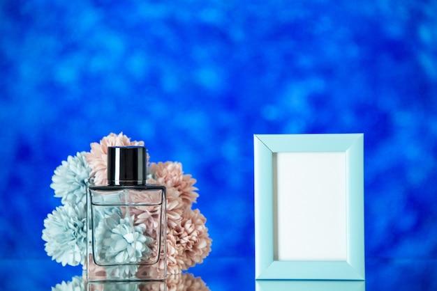 Vista frontale bottiglia di profumo piccola cornice blu fiori su sfondo blu spazio libero