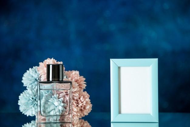 Vista frontale bottiglia di profumo piccola cornice blu fiori su sfondo blu scuro spazio libero
