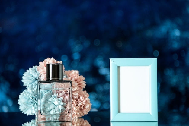 Front view perfume bottle small blue picture frame flowers on dark blue background