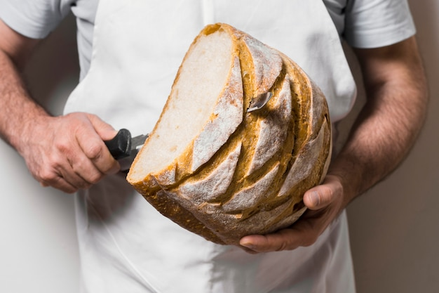 Front view person cutting slices of bread