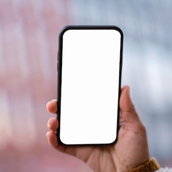 Вид спереди человек, держащий смартфон с пустым экраном