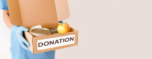 Vista frontale della scatola della tenuta della persona di donazione dell'alimento con lo spazio della copia