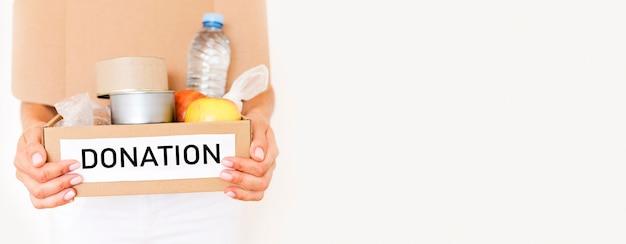 Vista frontale della persona che tiene la scatola di donazione di cibo