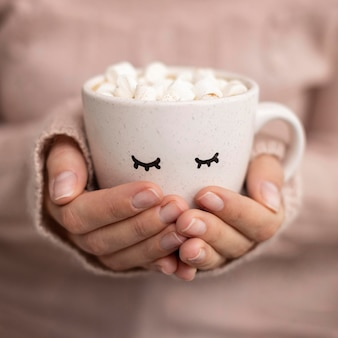 Front view of person holding cup of hot cocoa with marshmallows