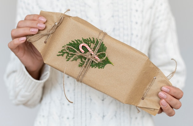 Front view of person holding decorated christmas gift with candy cane