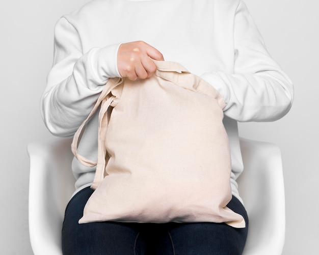 Front view person holding fabric tote bag