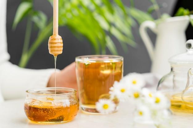 Человек вид спереди держит стакан с чаем и медом ковш