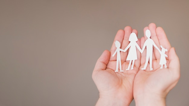 Front view person holding in hands cute paper family with copy space