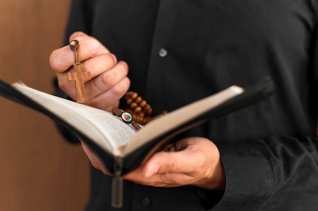Front view of person holding holy book and rosary