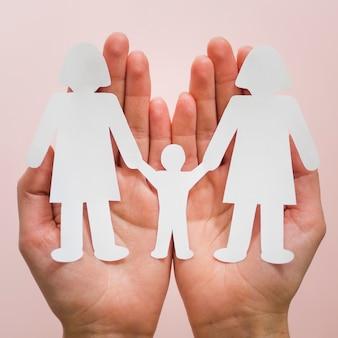 Человек вид спереди держит в руках милые бумажные семьи лгбт