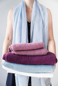 Front view person holding stacked towels