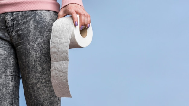Front view of person holding toilet paper roll with copy space