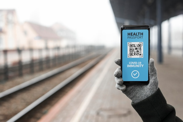 Front view of person holding virtual health passport on smartphone