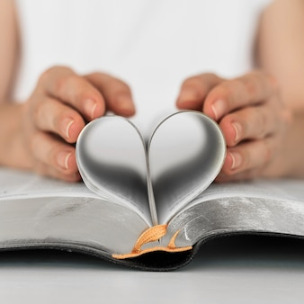 Front view of person making heart from holy book pages