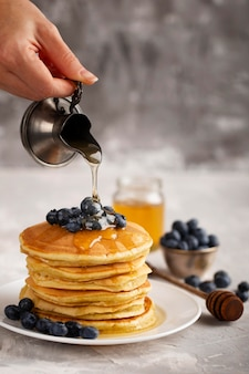 Front view person pouring maple syrop on pancakes