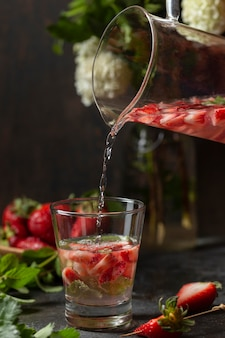 Front view person pouring strawberry infused water