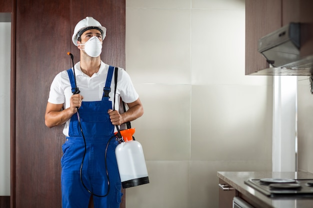 Front view of pest worker spraying in kitchen