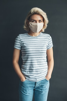 Фотография вид спереди женщины с медицинской маской на лице, позирующей перед камерой в повседневной одежде на темно-серой стене студии