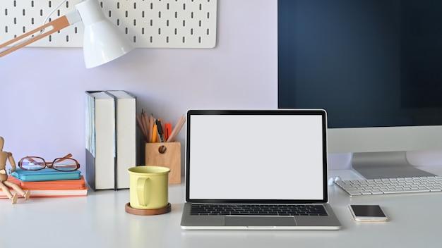 현대 책상의 전면보기 사진입니다. 화이트 빈 화면 노트북, 커피 컵, 램프, 모바일, 책, 연필 홀더, 안경 및 컴퓨터 책상에.