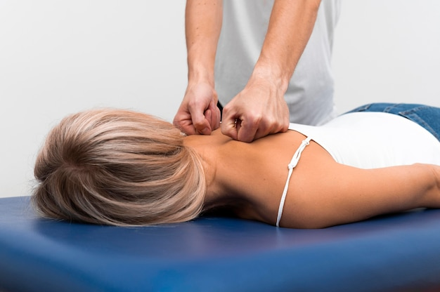 Front view of physiotherapist massaging female patient's back