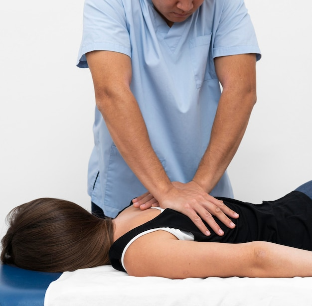 Front view of physiotherapist massaging woman's back