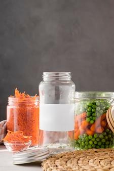 Vista frontale di piselli marinati e carotine in vasetti di vetro trasparente con spazio di copia