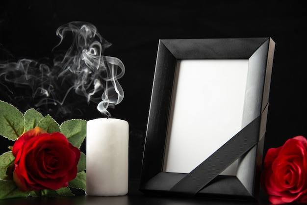 Front view of picture frame with candle and red flowers on dark