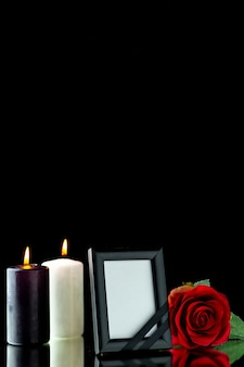 Front view of picture frame with candle and red rose on black