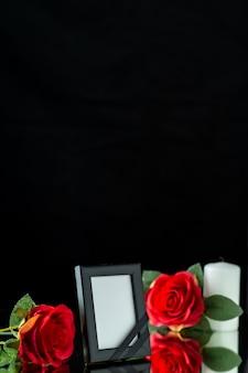 Vista frontale della cornice con candela e rosa rossa su fondo nero
