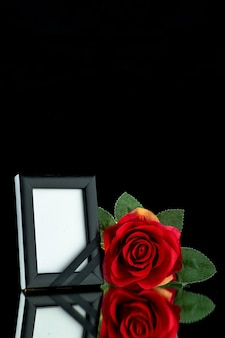Front view of picture frame with red rose on black