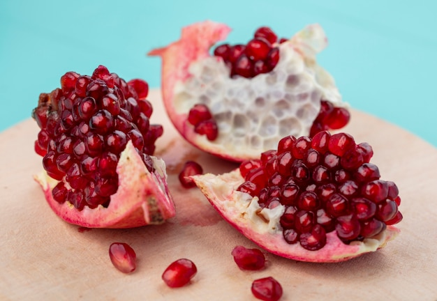 Front view of pieces of pomegranate on a cutting board